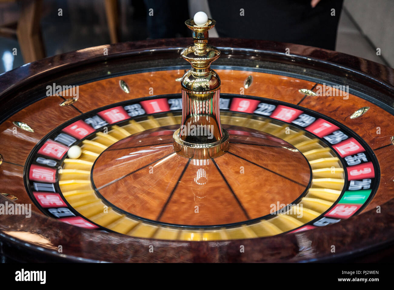 Roulette spinning, in movement, during a demo game. Roulette is a gambling and betting casino game  Picture of a roulette turning fast with a white ba - Stock Image