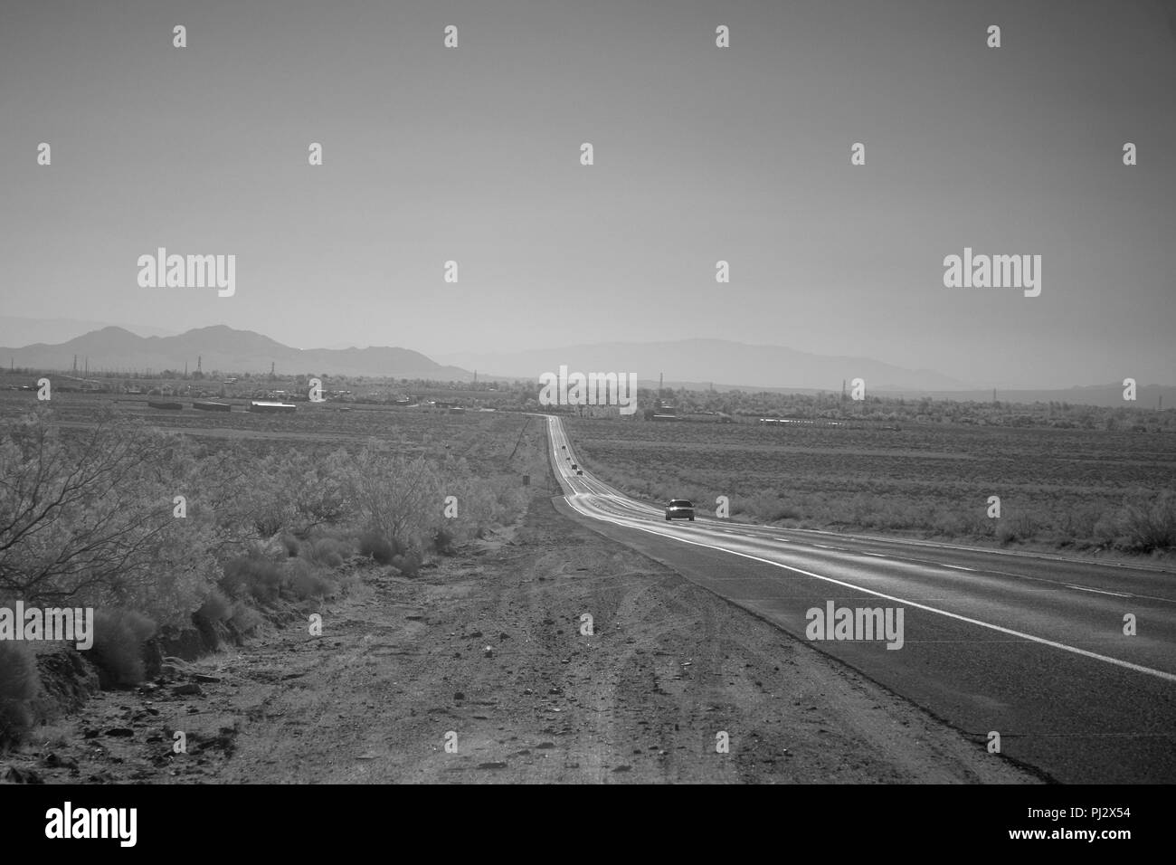 A lonely desert highway leading down into a valley with hazy mountains beyond. - Stock Image