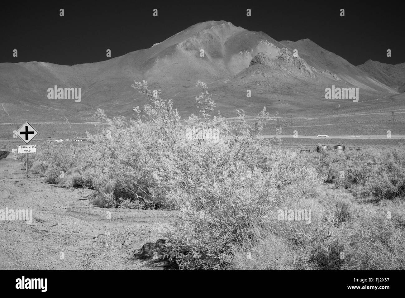 Highway sign and desert brush with tall barren mountains under a black sky. - Stock Image