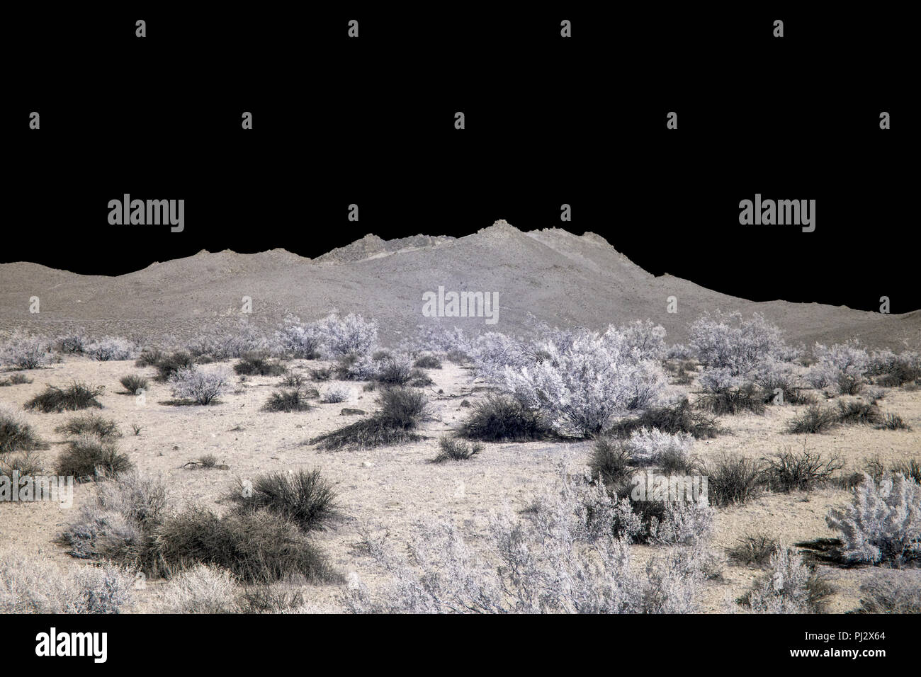 Desert valley with mountains under a black sky. - Stock Image