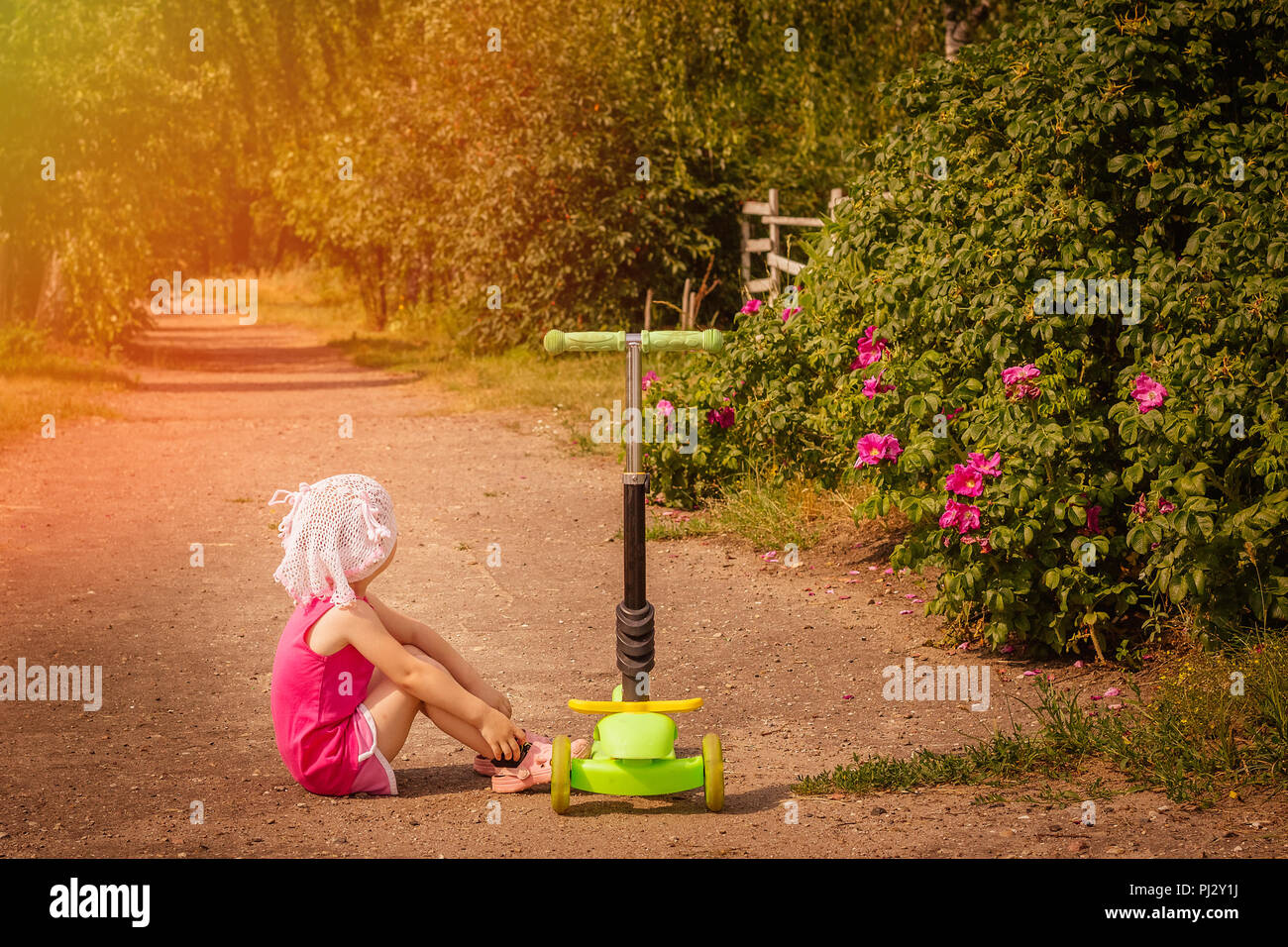 A little girl is sitting on the road next to a scooter in the countryside in the rays of a bright warm sun Stock Photo