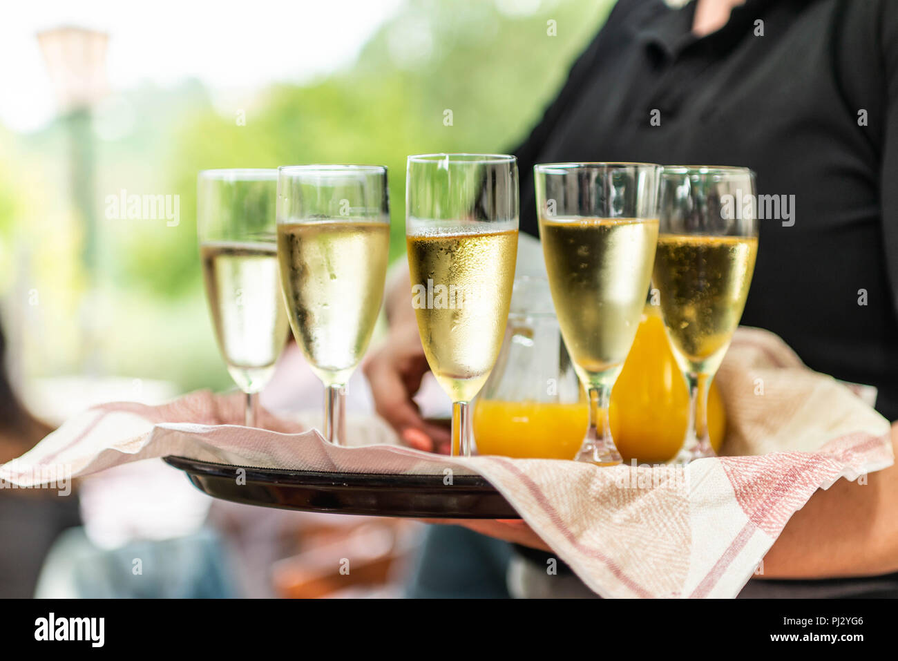 Champagne or sparkling wine in glasses in restaurant served by servant. - Stock Image
