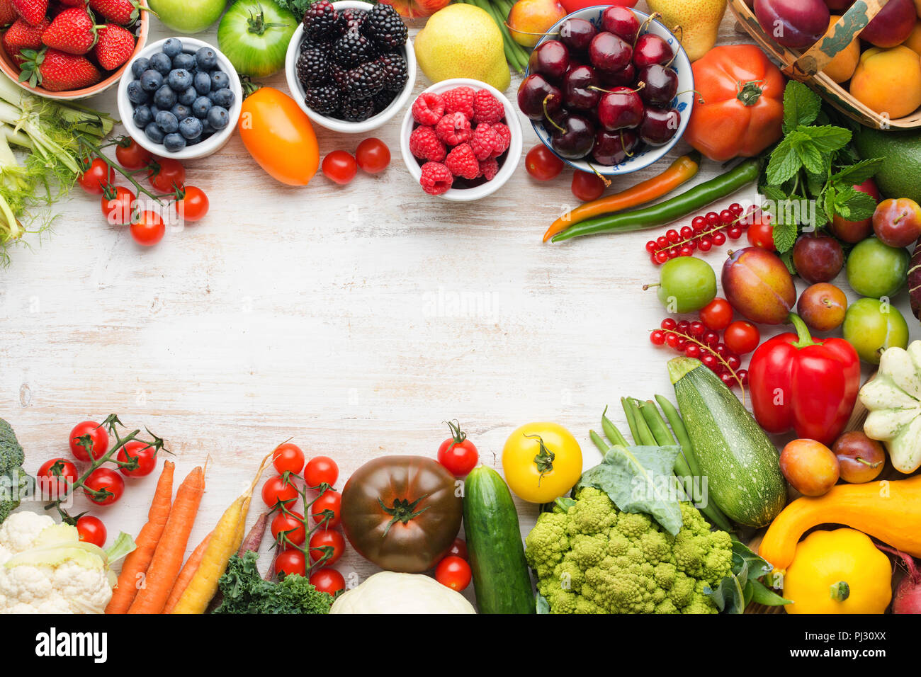 Healthy eating, summer fruits vegetables berries, cherries peaches strawberries cabbage broccoli cauliflower squash tomatoes carrots spring onions beans beetroot, copy space, top view, selective focus Stock Photo