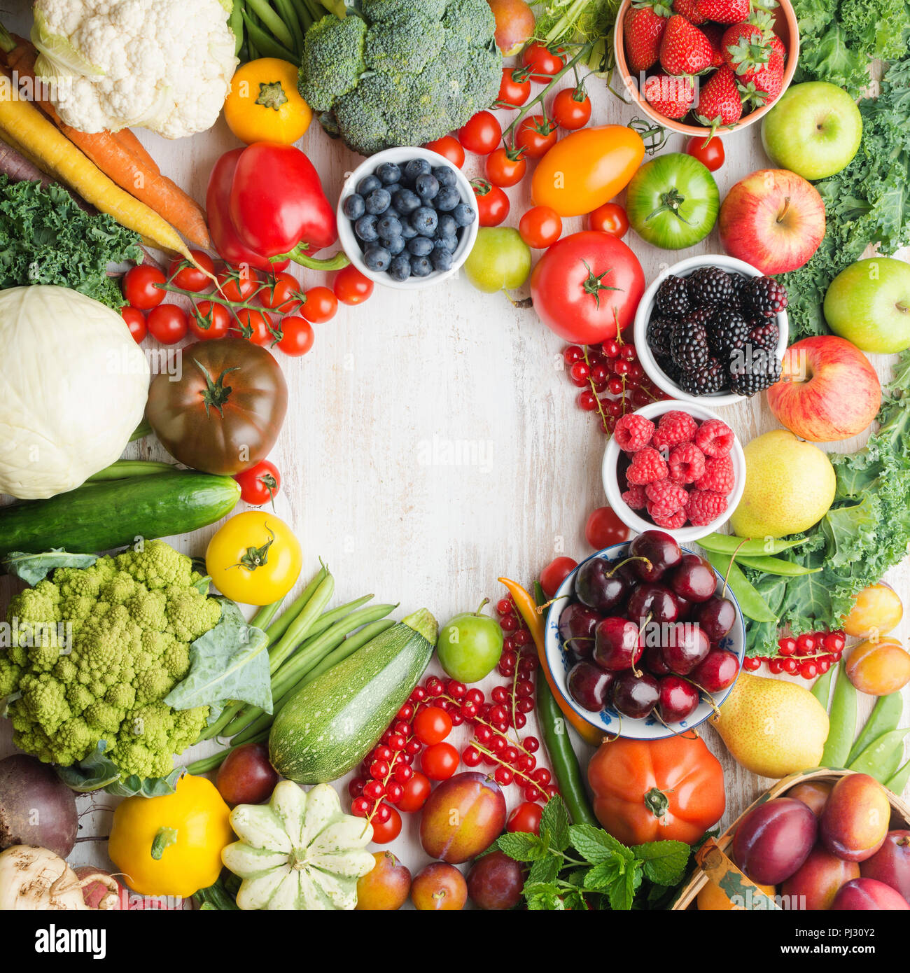 Fresh fruits vegetables berries arranged in a circle frame, cherries peaches strawberries cabbage broccoli cauliflower squash tomatoes carrots beetroot, copy space, top view, aquare selective focus Stock Photo
