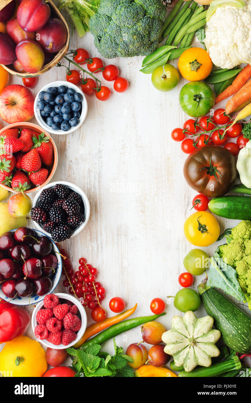 Healthy summer fruits vegetables berries arranged in a frame, cherries peaches strawberries cabbage broccoli cauliflower squash tomatoes carrots beetroot, copy space, top view, selective focus Stock Photo