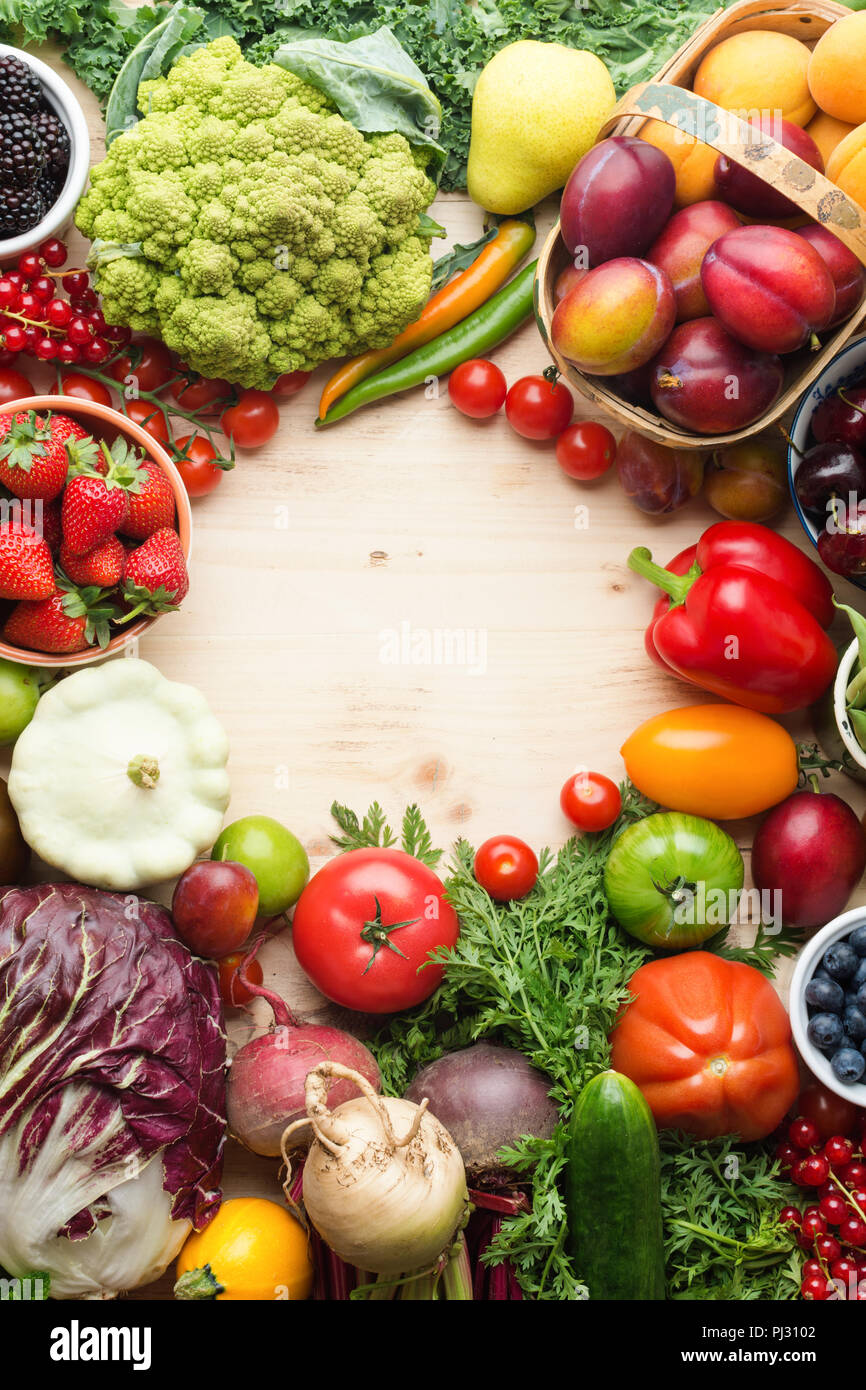 Fresh farm fruits vegetables berries, cherries apricots strawberries cabbage broccoli cauliflower squash tomatoes carrots spring onions beans beetroot, pepper, copy space, top view, selective focus Stock Photo