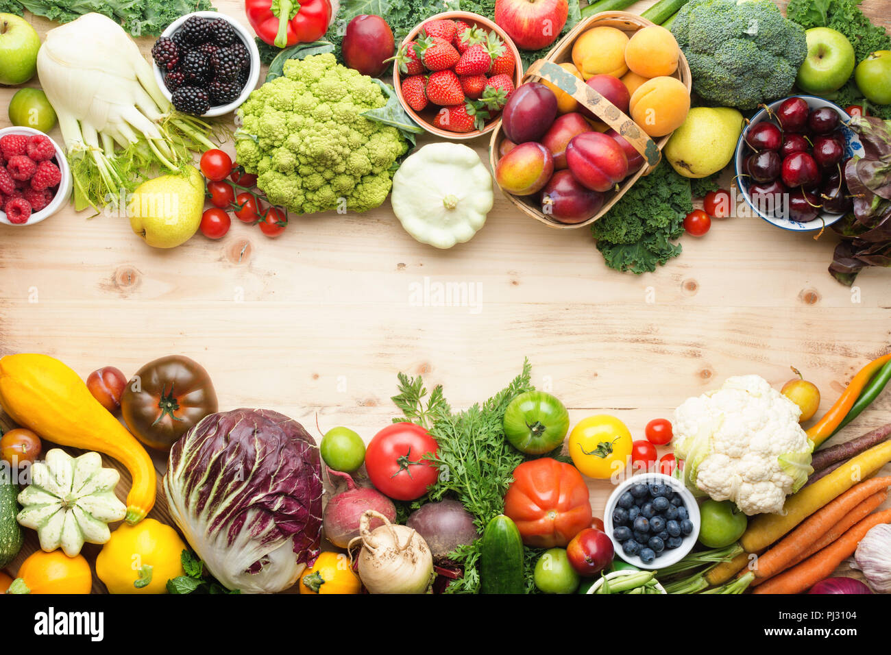 Fresh organic fruits vegetables berries, cherries apricots strawberries cabbage broccoli cauliflower squash tomatoes carrots spring onions beans beetroot, pepper, copy space, top view, selective focus Stock Photo