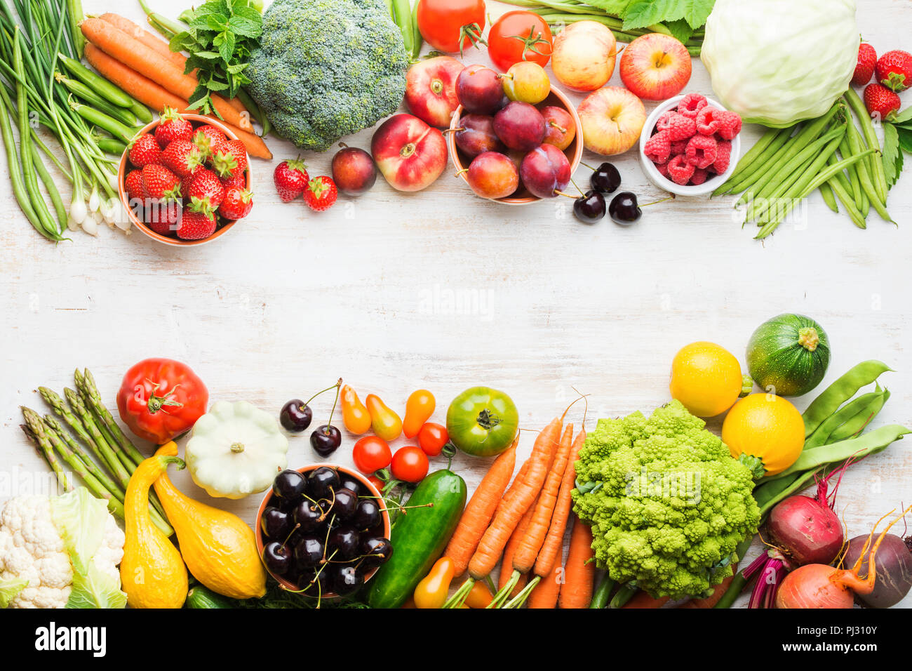 Summer fruits vegetables berries, apples cherries peaches strawberries cabbage broccoli cauliflower squash tomatoes carrots spring onions beans beetroot, copy space, top view, selective focus Stock Photo