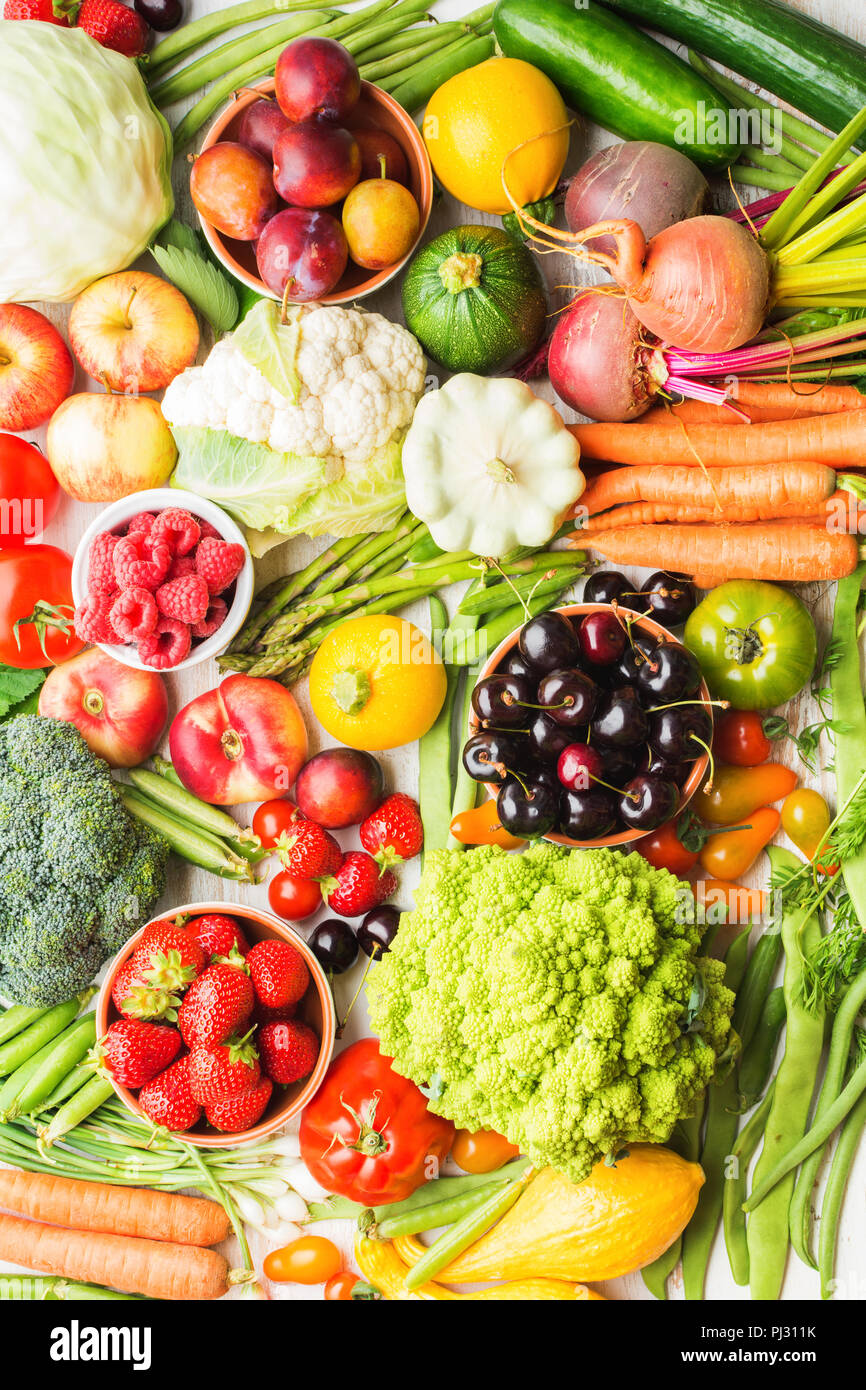 Summer fruits vegetables berries background, apples cherries peaches strawberries cabbage broccoli cauliflower squash tomatoes carrots spring onions beetroot, top view, selective focus Stock Photo