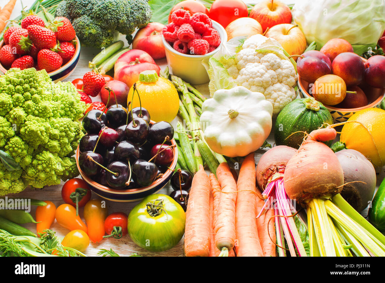 Lots of summer fruits vegetables berries, apples cherries peaches strawberries cabbage broccoli cauliflower squash tomatoes carrots spring onions beans beetroot, selective focus - Stock Image
