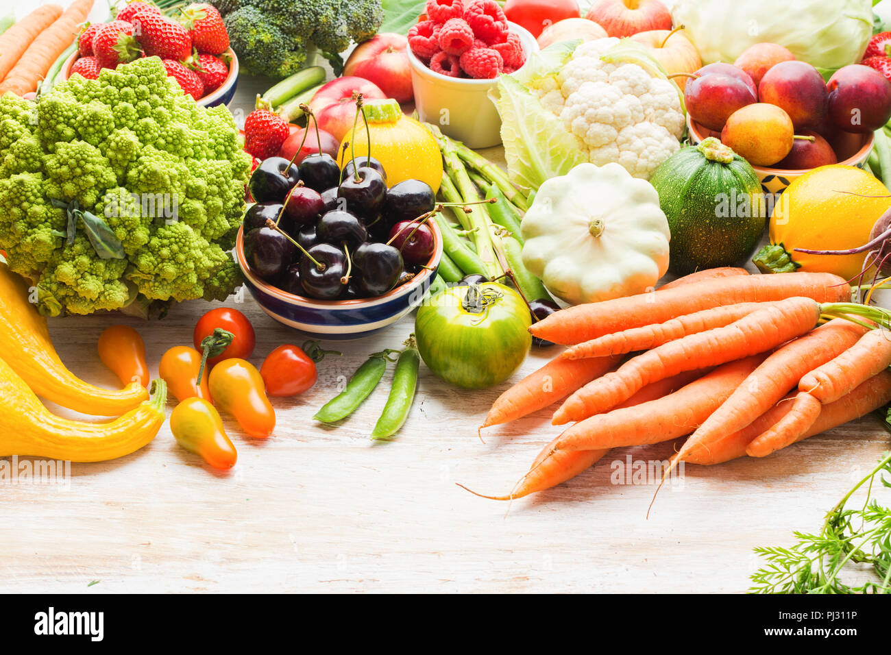 Lots of summer fruits vegetables berries, apples cherries peaches strawberries cabbage broccoli cauliflower squash tomatoes carrots spring onions beans beetroot, copy space, selective focus - Stock Image