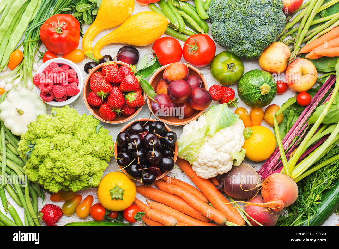 Summer fruits vegetables berries background, apples cherries peaches strawberries cabbage broccoli cauliflower squash tomatoes carrots spring onions beetroot, top view, selective focus - Stock Image