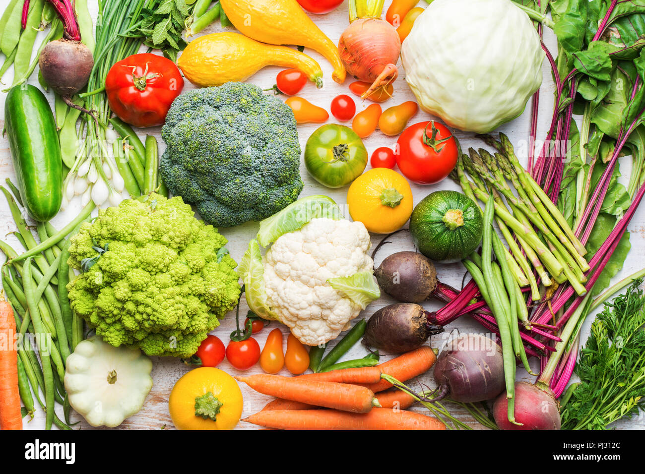 Colorful organic vegetables background on white wooden table, healthy background, broccoli cauliflower tomatoes spring onions cucumbers carrots beetroot, top view, selective focus - Stock Image