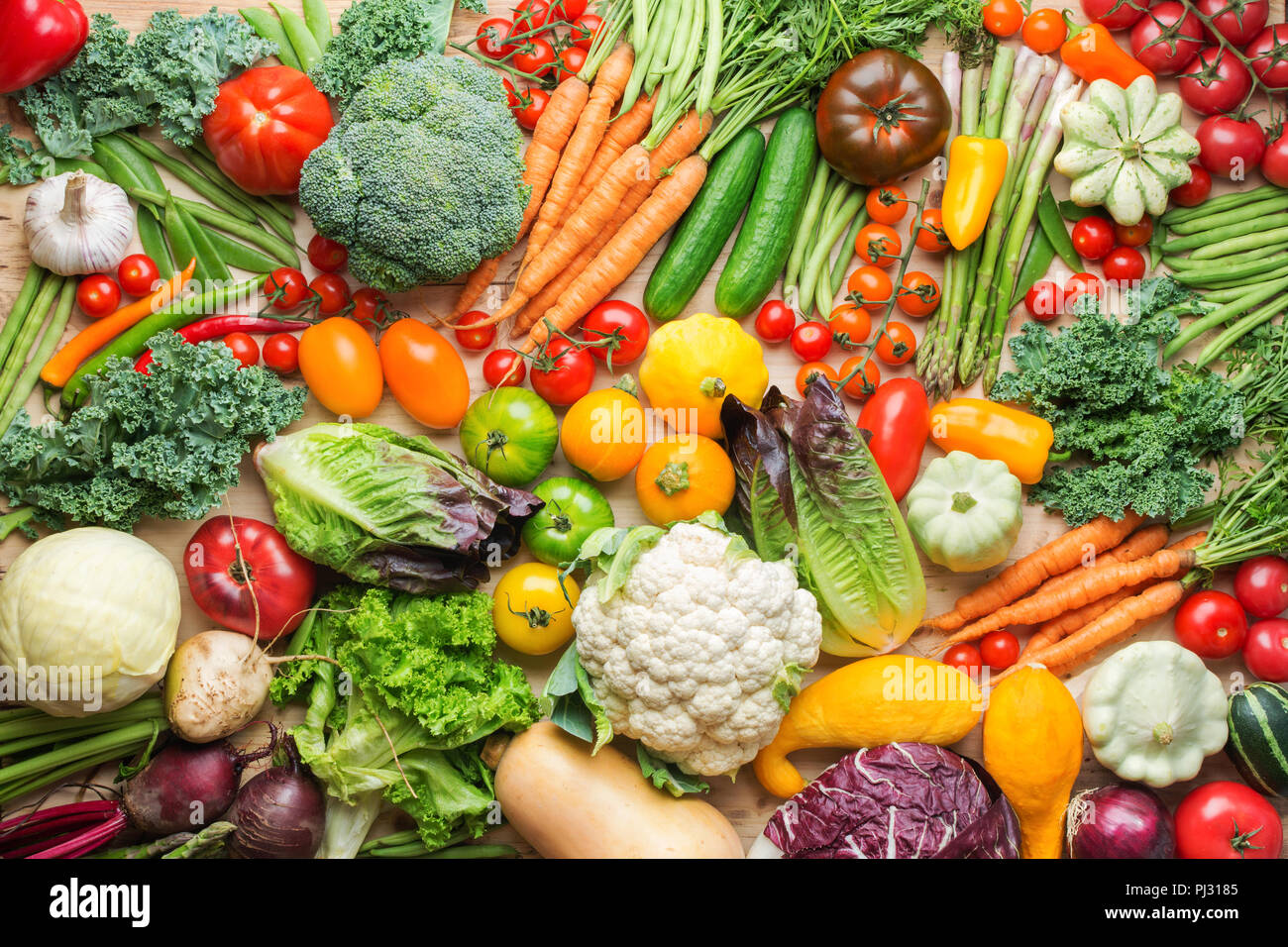 Assortment of fresh colorful organic vegetables on wooden pine table, healthy food background, top view, selective focus - Stock Image
