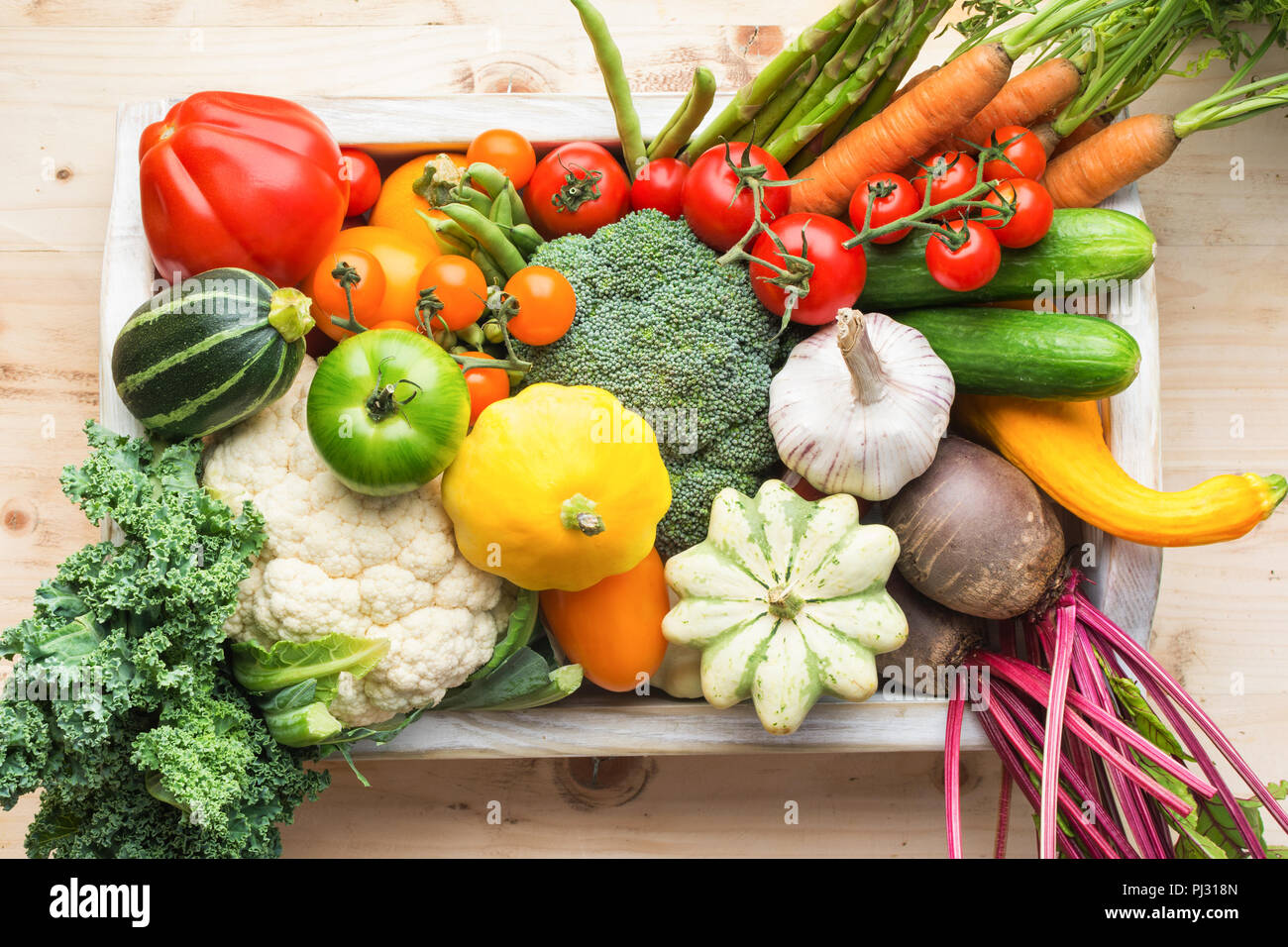 Fresh organic vegetables in a white tray on wooden pine table, top view, selective focus - Stock Image