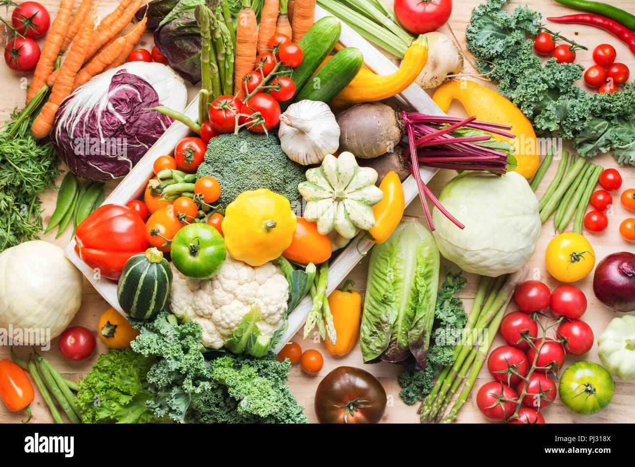 Assortment of fresh colorful organic vegetables in white tray on wooden pine table, food background, top view, selective focus - Stock Image