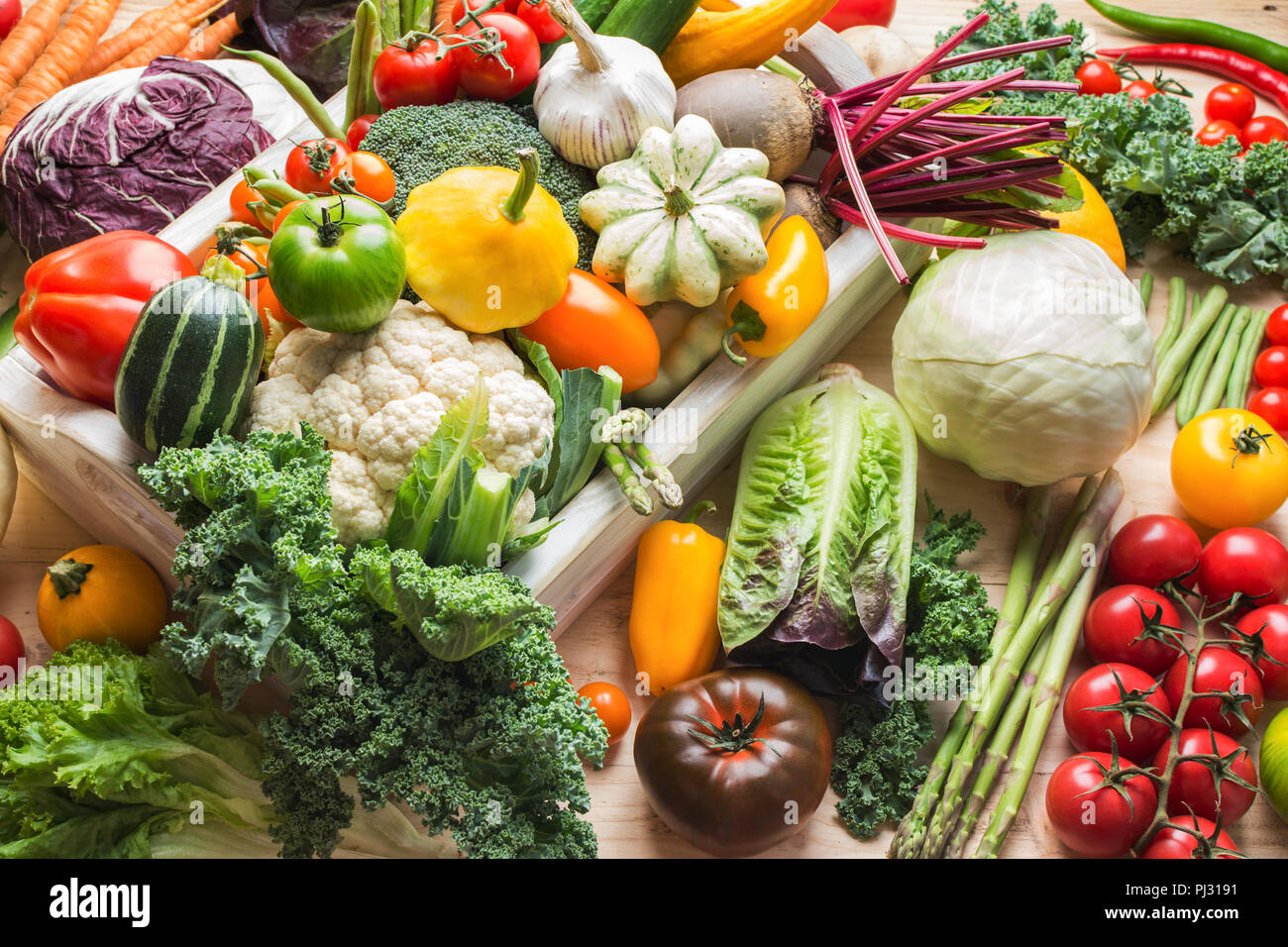 Assortment of fresh colorful organic vegetables in white tray on wooden pine table, food background, selective focus - Stock Image