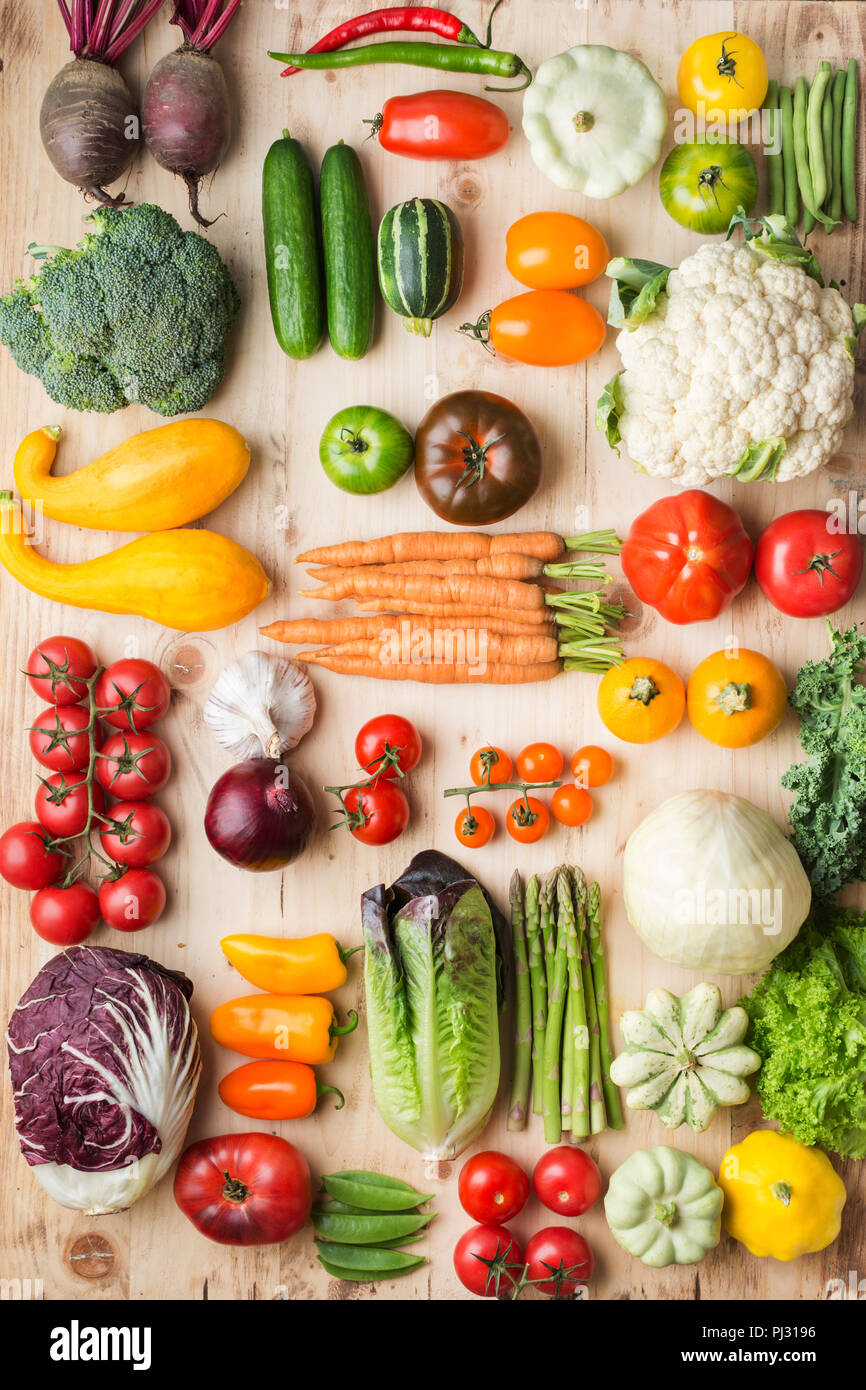 Assortment of fresh colorful organic vegetables on wooden pine table, creative food background in a grid, vertical, top view, selective focus Stock Photo