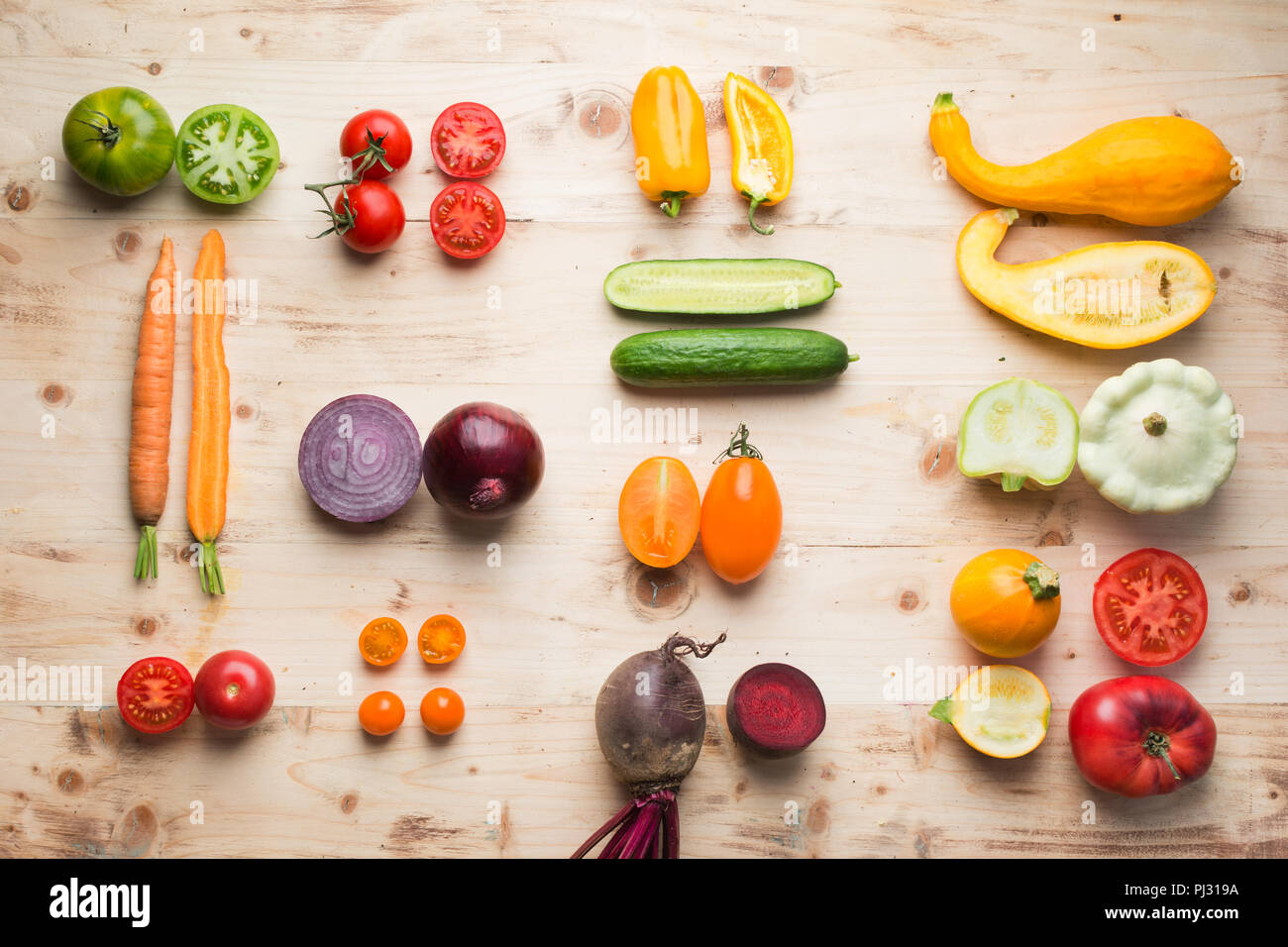 Creative food background in a grid, assortment of fresh colorful organic vegetables whole and cut part on wooden pine table, vertical, top view, selective focus - Stock Image