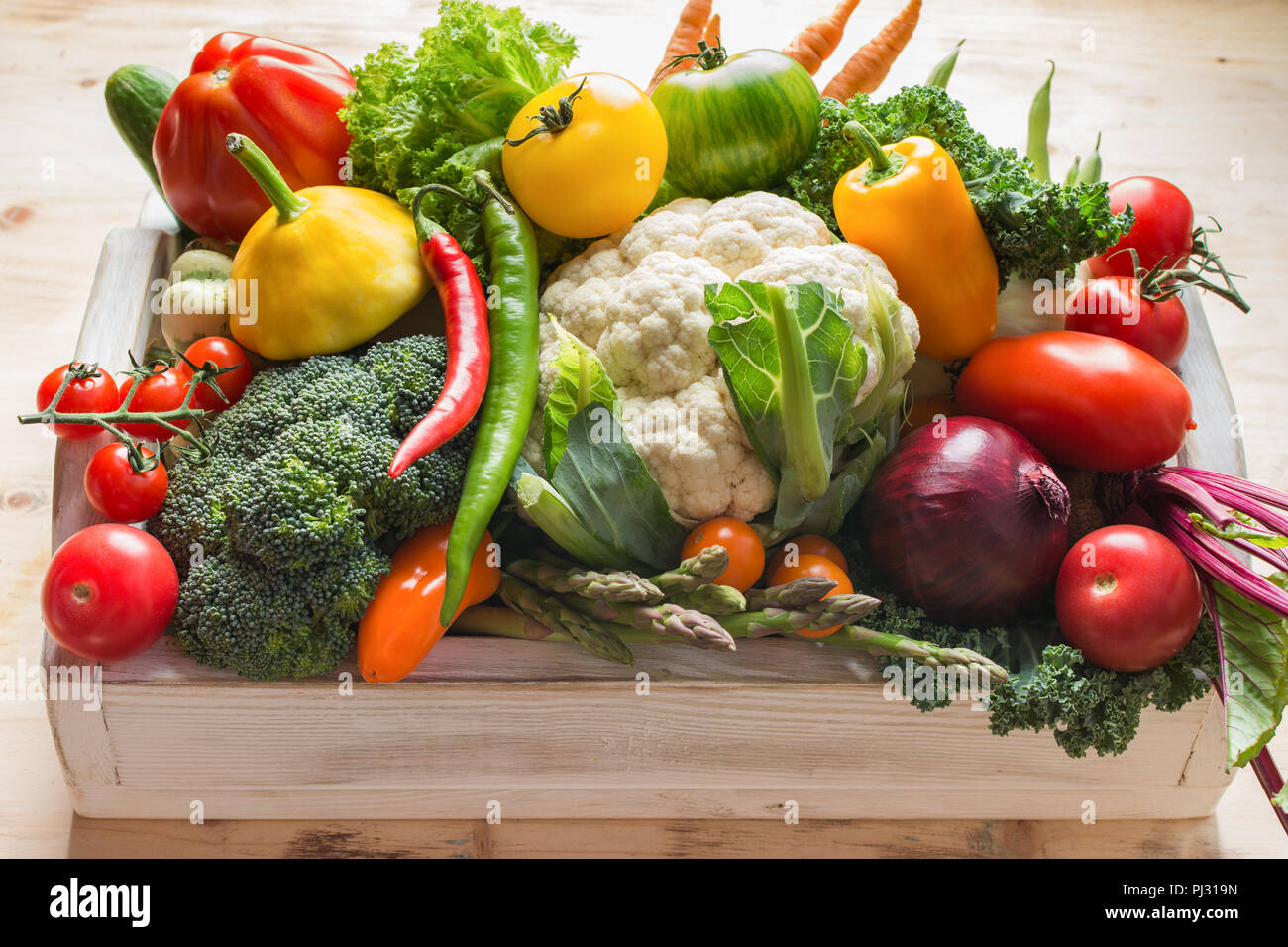 Fresh organic colorful vegetables in a white tray on wooden pine table, close up, selective focus - Stock Image