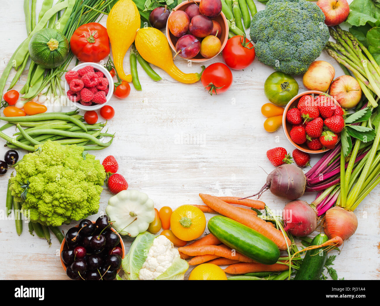 Colourful farm fruits vegetables berries, apples cherries peaches strawberries cabbage broccoli cauliflower squash tomatoes carrots spring onions beans beetroot, copy space, top view Stock Photo