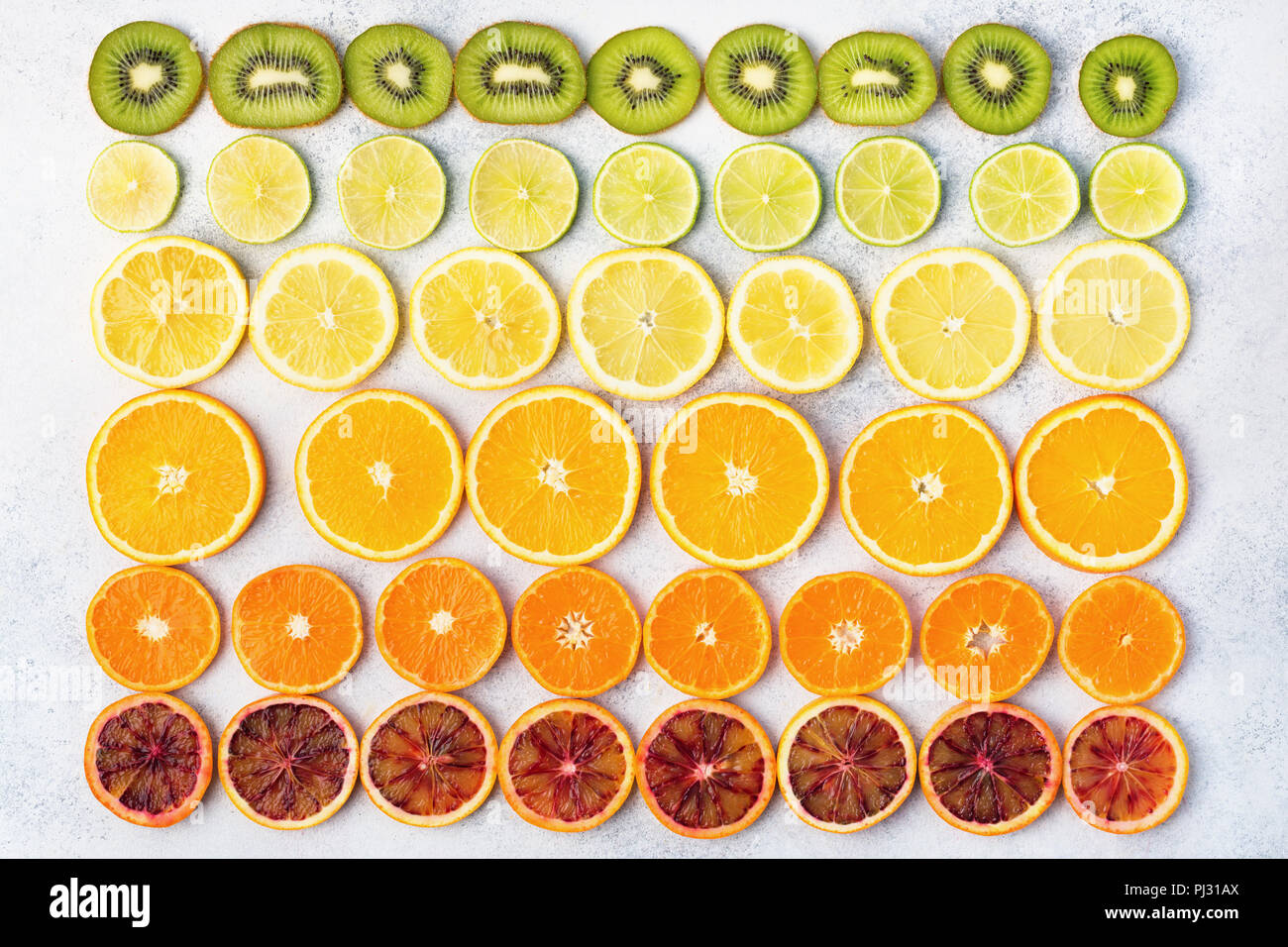 Different varieties of citrus fruits, oranges, lemons, limes, kiwis arranged in the rows. Colorful background, top view - Stock Image