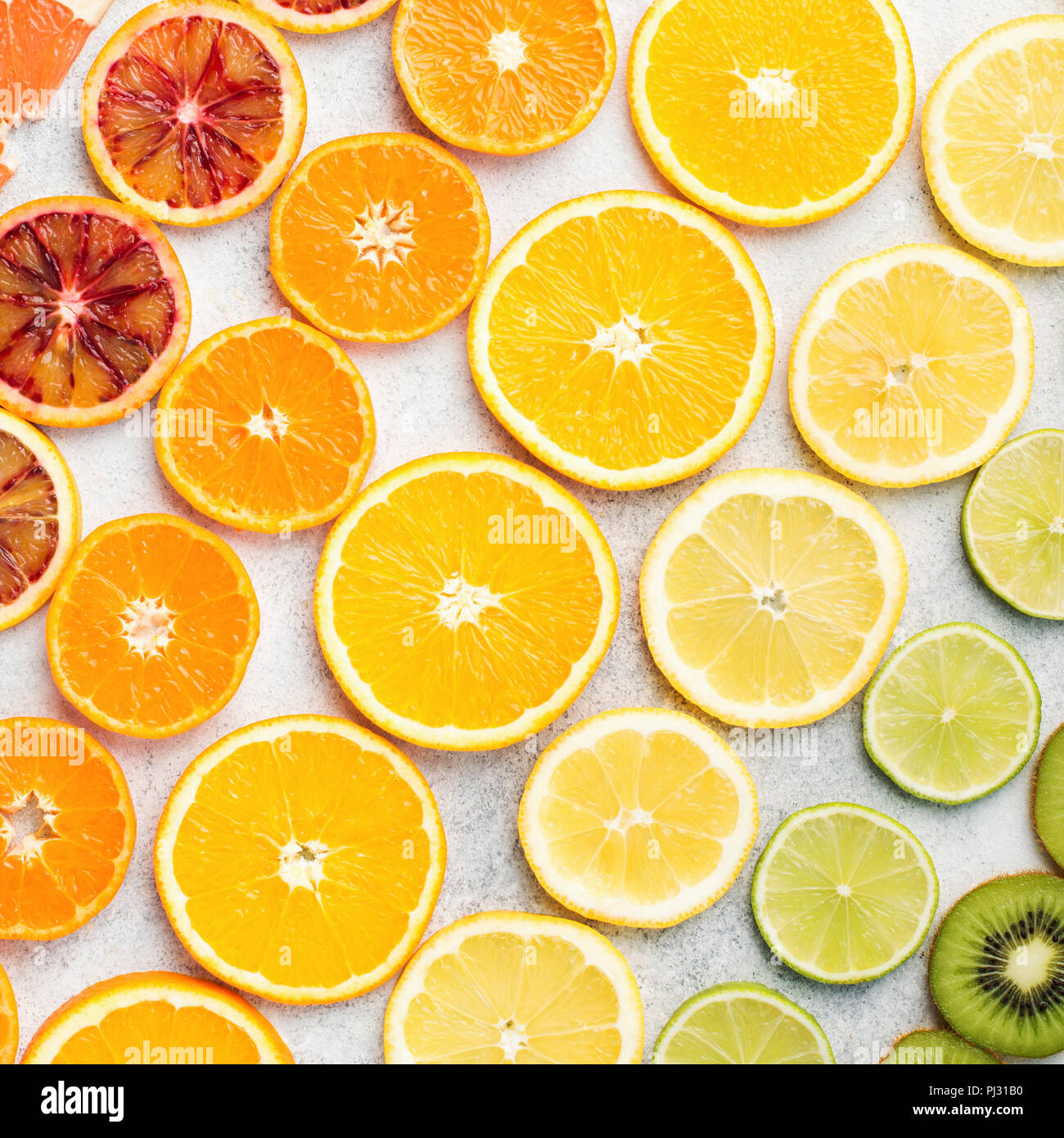 Different varieties of citrus fruits, oranges, lemons, limes, kiwis arranged in the rows, diagonal, square. Colorful background, top view - Stock Image