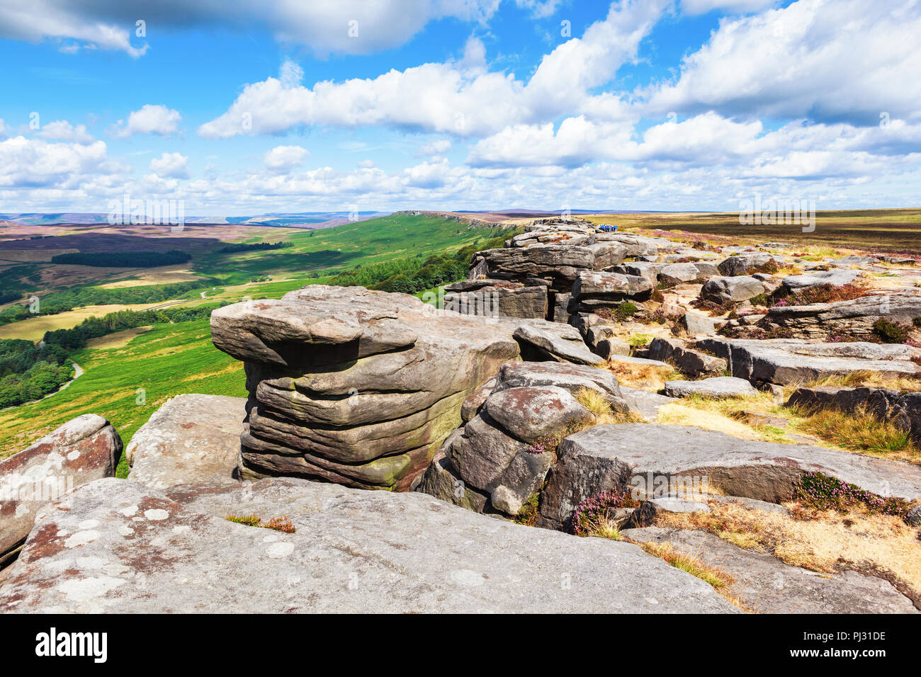 Rock formations in Stanage edge, with the fields and pastures on the background. Peak District National Park, Derbyshire, England , selective focus - Stock Image