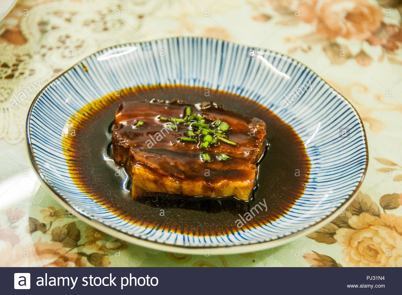 A traditionally home cooked hongshaorou dish which has been cooked for many hours at the Yu's home in an old style Shanghai building. - Stock Image
