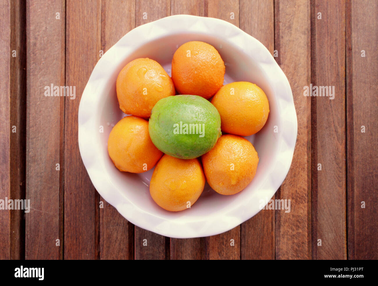 A round white bowl of six mandarin oranges and one green lime sits on a wood slat background. Stock Photo