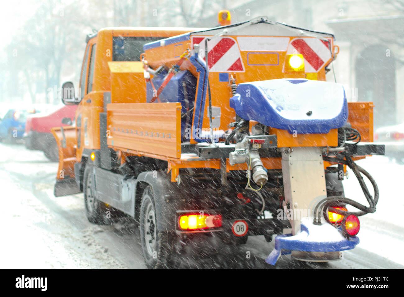 Spreader truck in winter snow blizzard weather - Stock Image