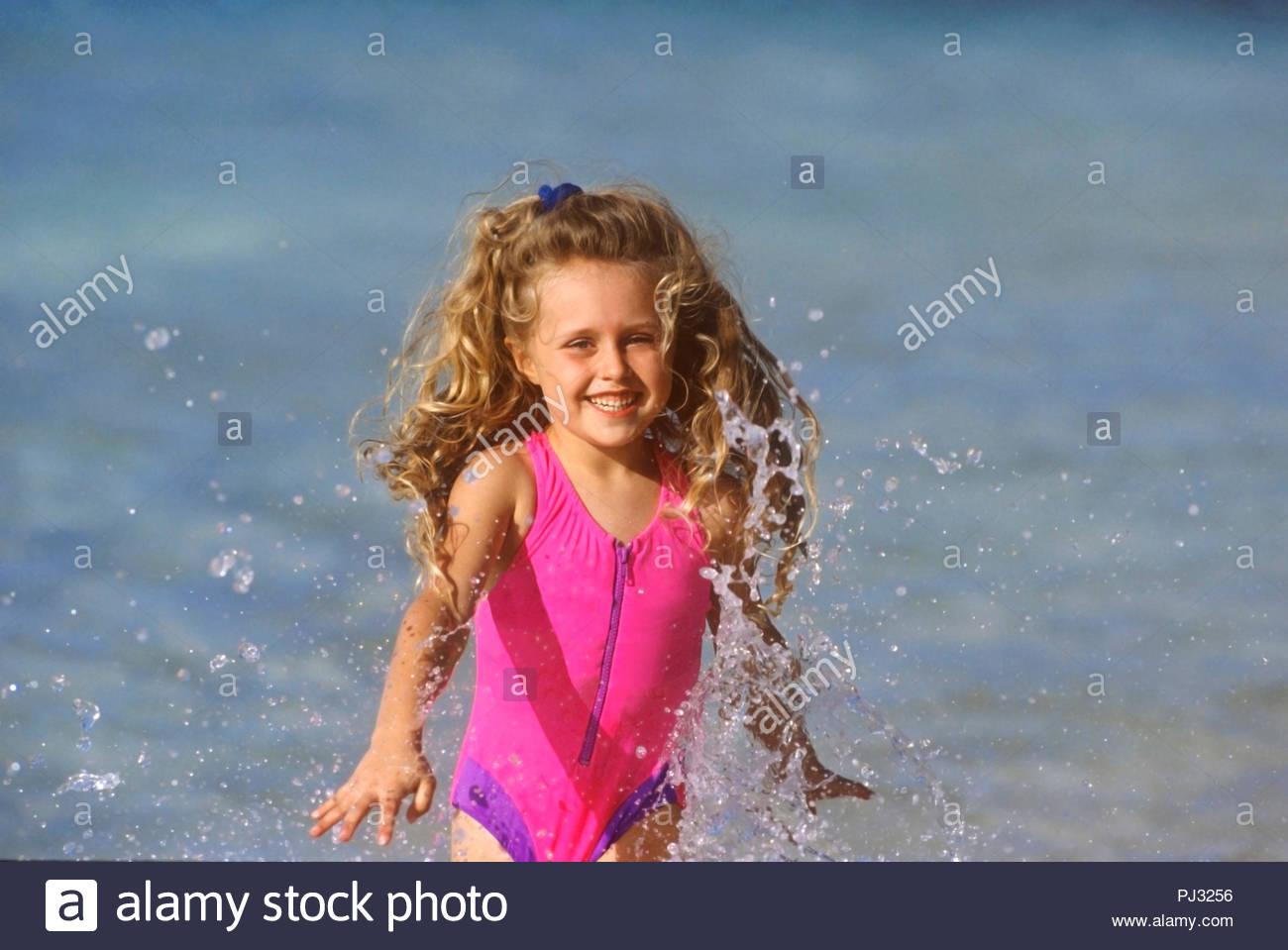 girl splashing in waves on beach Stock Photo