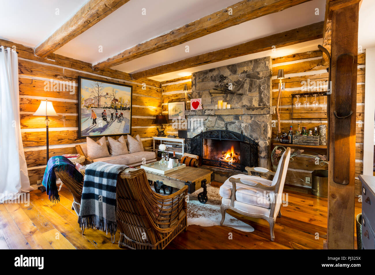 living room with fireplace in log house - Stock Image