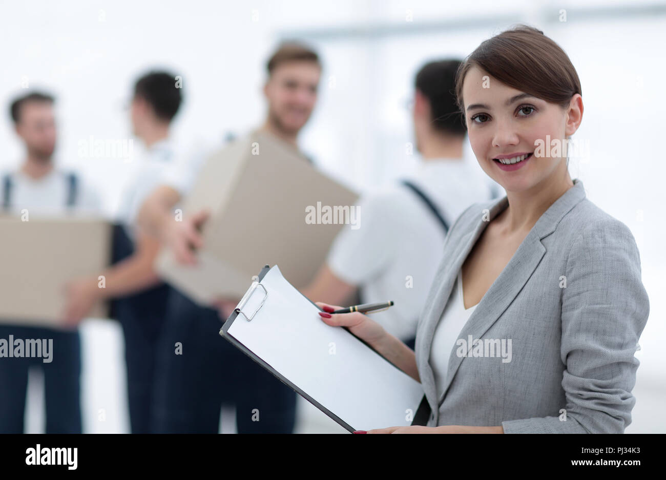 Businessman with documents, creating a stack of cardboard boxes. - Stock Image