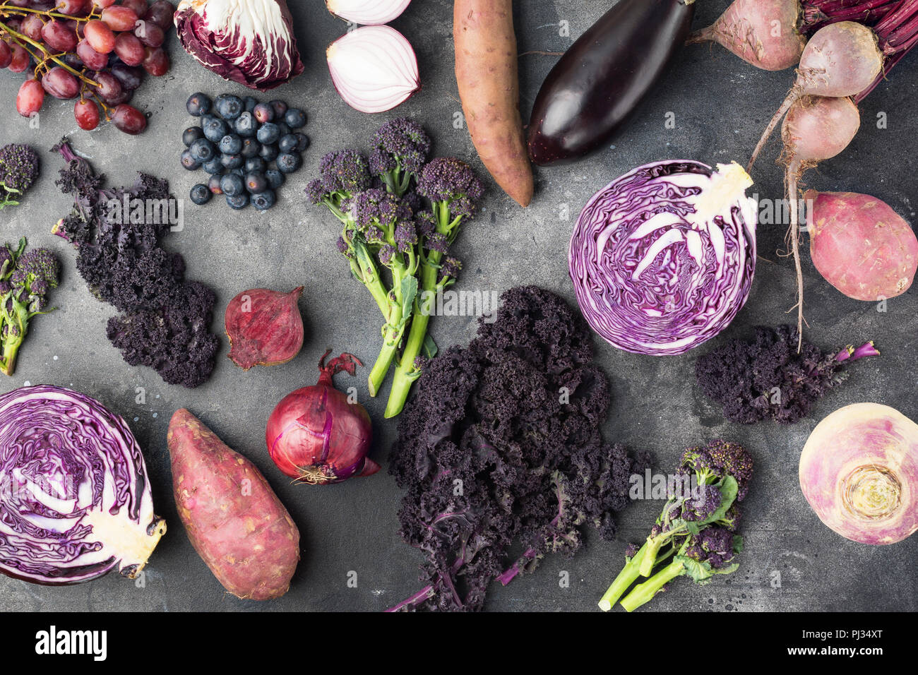 Vegetables and fruits background in purple, green and dark red colours, cabbage kale sprouts sweet potato onions broccoli blueberries grapes, top view, dark grey background, selective focus - Stock Image