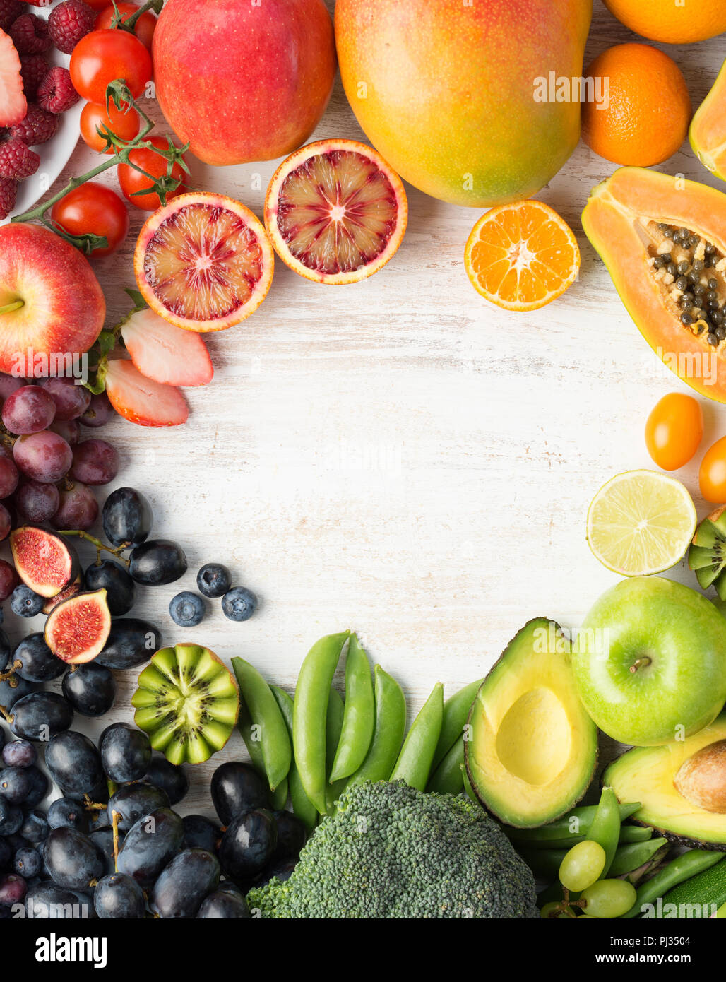 Healthy eating, varieity of fruits and vegetables in rainbow colours on the off white table arranged in a frame with copy space, vertical top view, selective focus Stock Photo