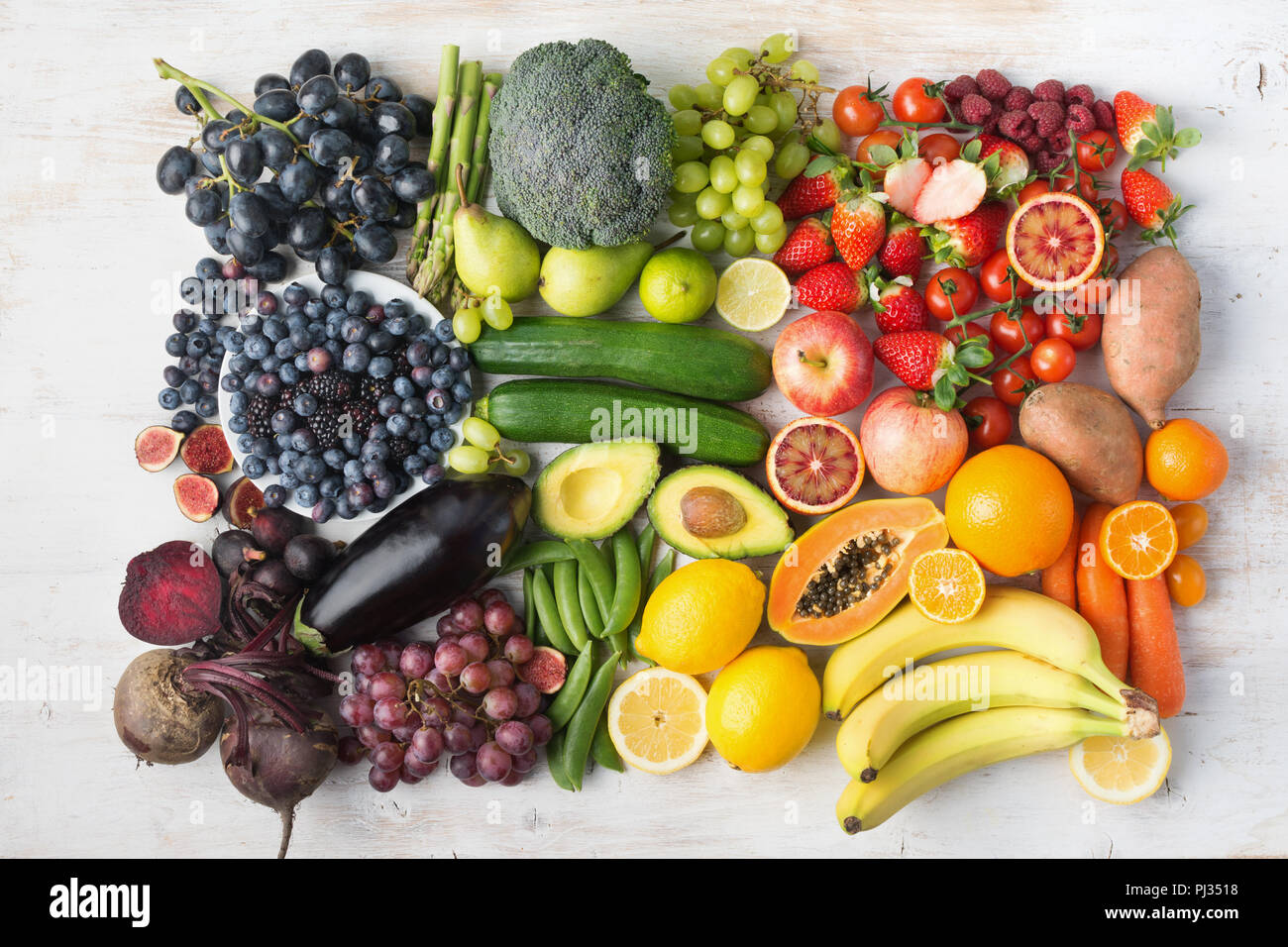 Healthy eating concept, assortment of rainbow fruits and vegetables, berries, bananas, oranges, grapes, broccoli, beetroot on the off white table arranged in a rectangle, top view, selective focus Stock Photo