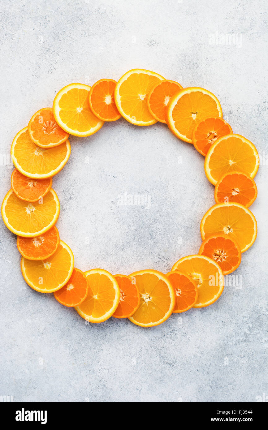 Circle background made of oranges and clementines on white table, top view, copy space, vertical, selective focus - Stock Image