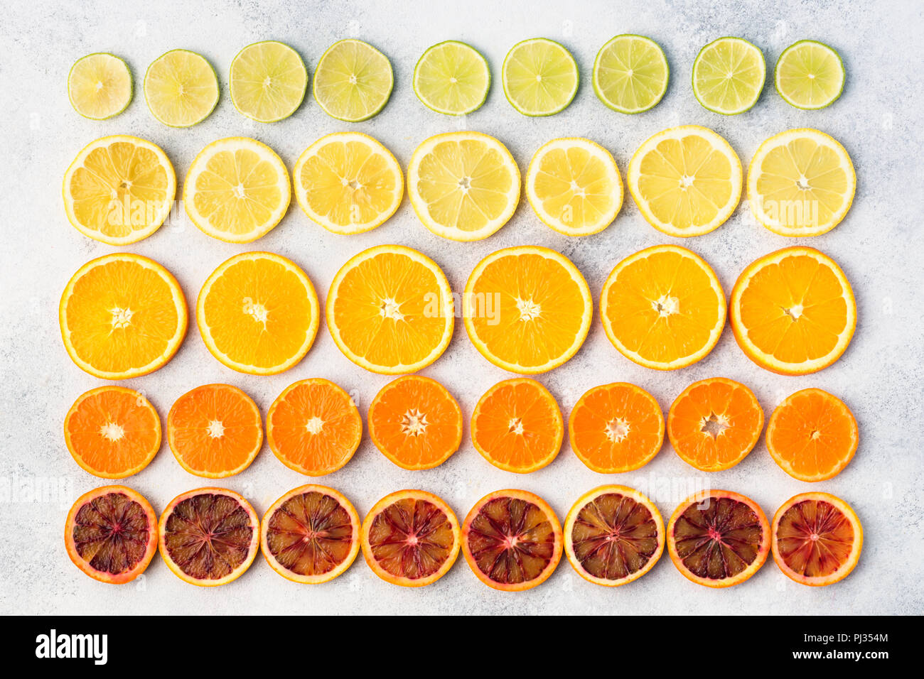 Citrus fruits rich in vitamin C, oranges, lemons, limes, satsumas arranged in the rows. Colorful background, top view - Stock Image
