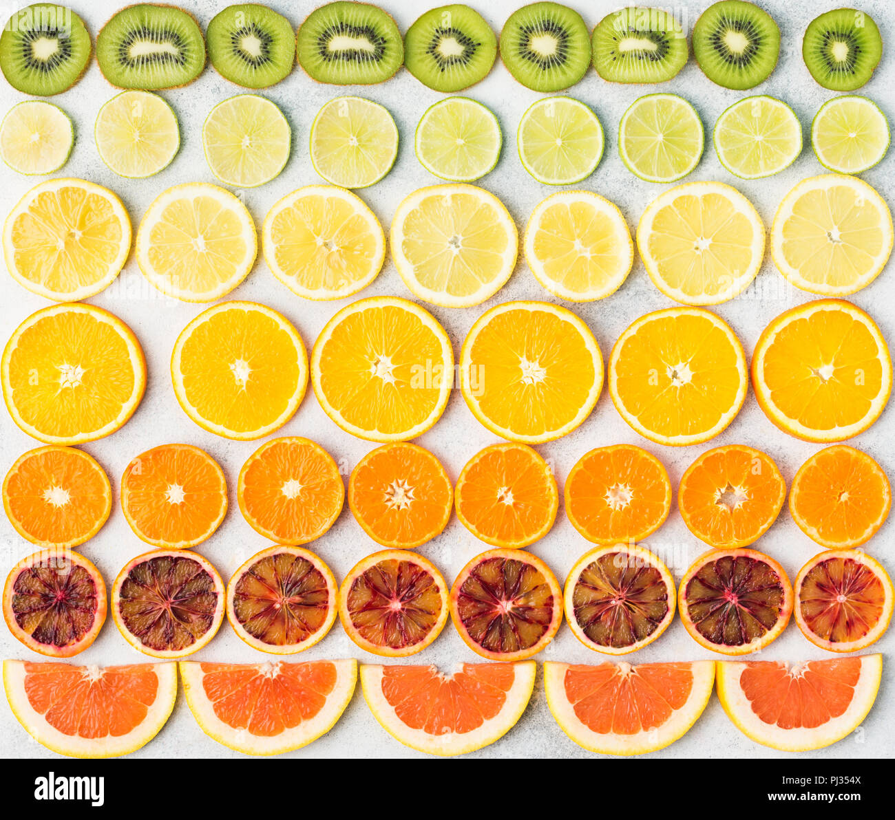 Sliced fruits rich in vitamin C, oranges, lemons, limes, satsumas, kiwis, grapefruits arranged in the rows. Colorful background, top view - Stock Image