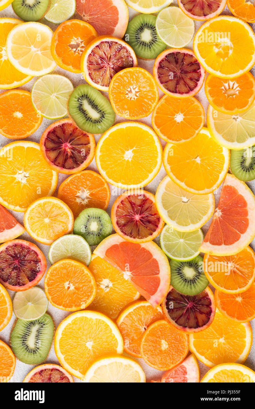 Colourful fruit pattern, oranges, clementines, blood oranges, kiwis and grapefruits on white table background, top view, selective focus - Stock Image