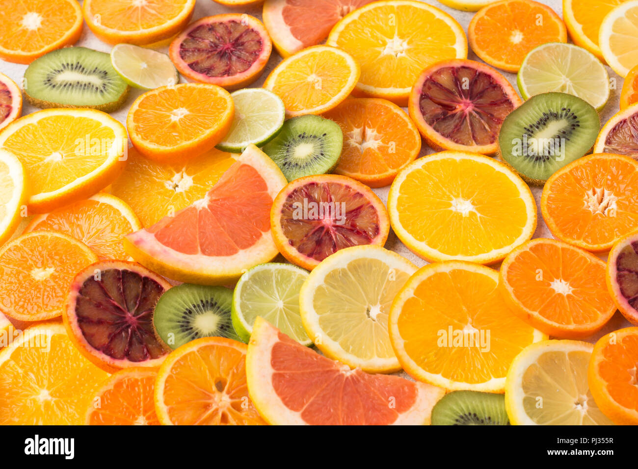 Colourful fruits background oranges, clementines, blood oranges, kiwis and grapefruits on white table, selective focus - Stock Image