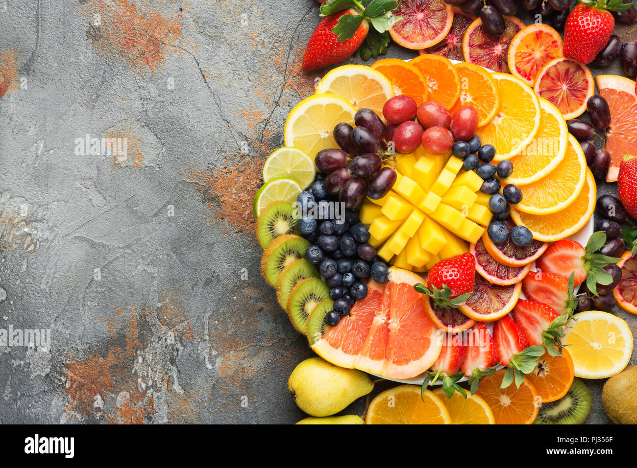 Colorful cut fruits in rainbow colors oranges grapes mango strawberries kiwis blueberries grapefruit on the grey concrete table, top view, copy space, selective focus Stock Photo