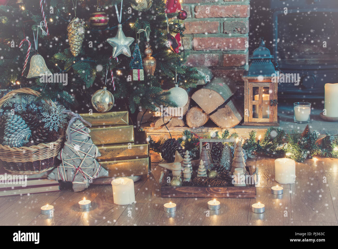 decorated fireplace with woodburner lit up christmas tree with baubles and ornaments lantern stars and garlands with drawn snow over the photo se