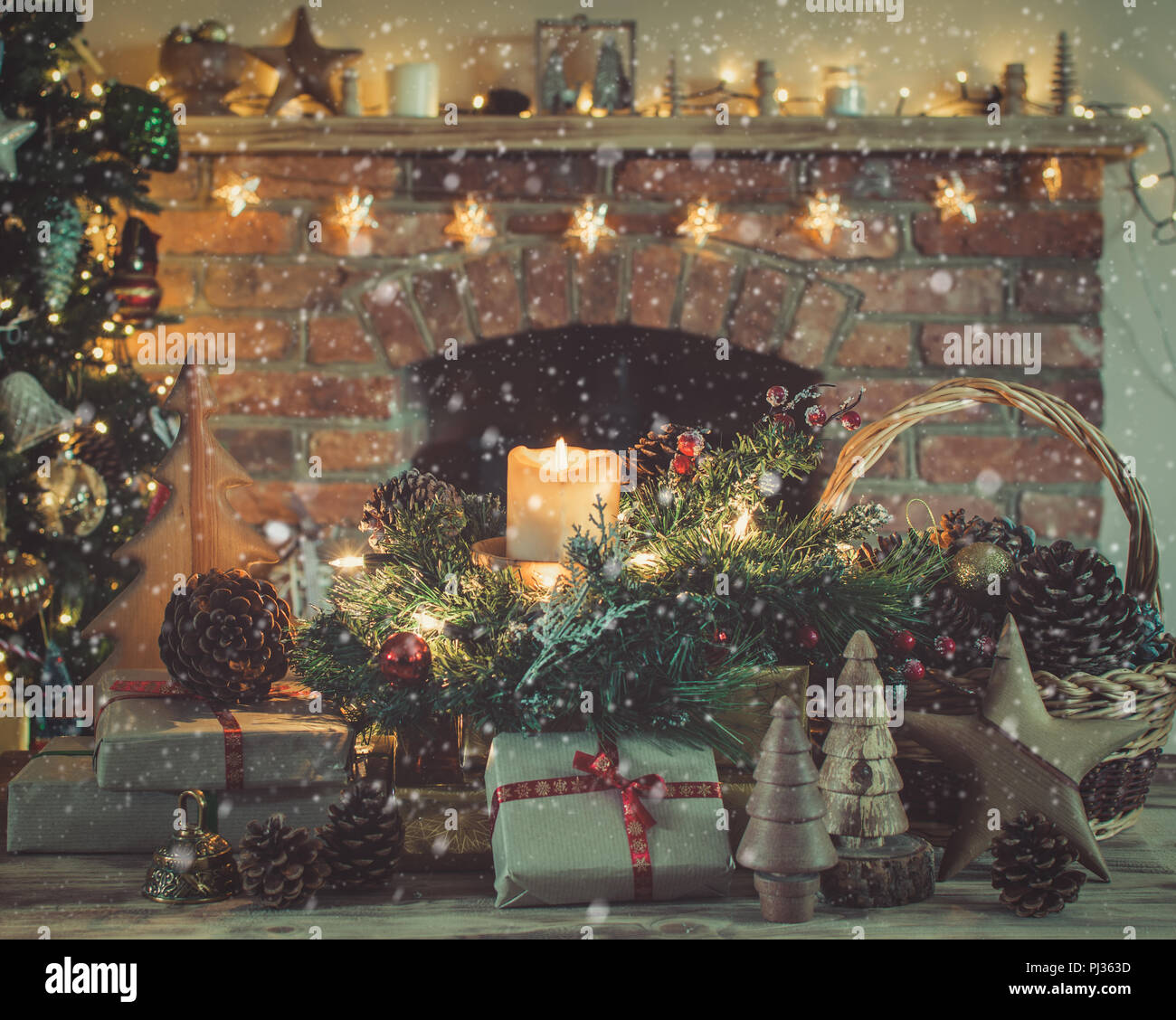 cosy christmas presents and decorations on the table in front of fireplace with woodburner lit up christmas tree with baubles and ornaments and garl