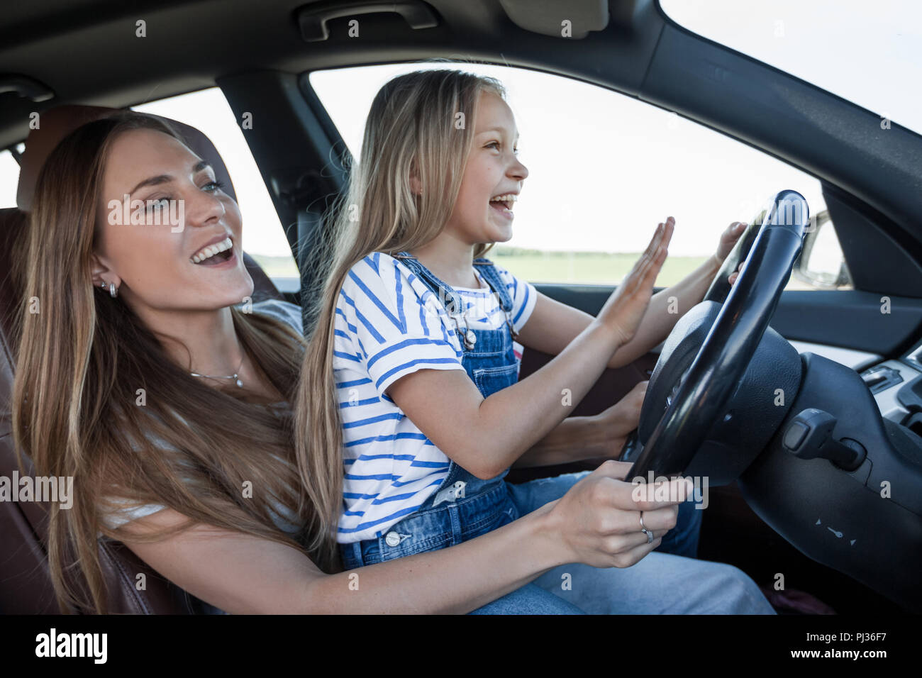 mom teaches her little daughter to drive - Stock Image
