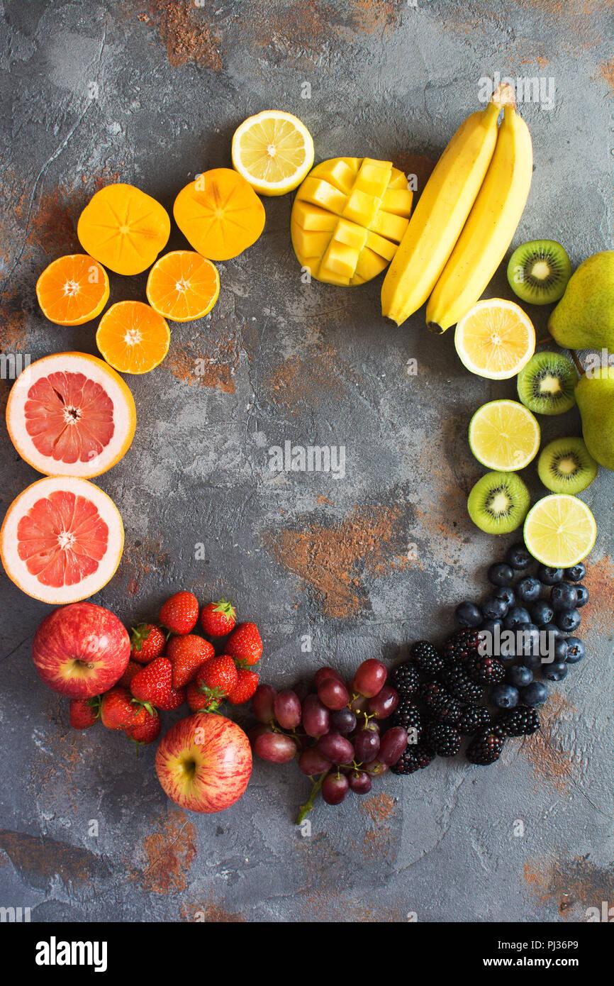 Rainbow colored fruits in a circle, strawberries, blueberries, mango, orange, grapefruit, banana, apple, grapes, kiwis, papaya on the grey background, Stock Photo