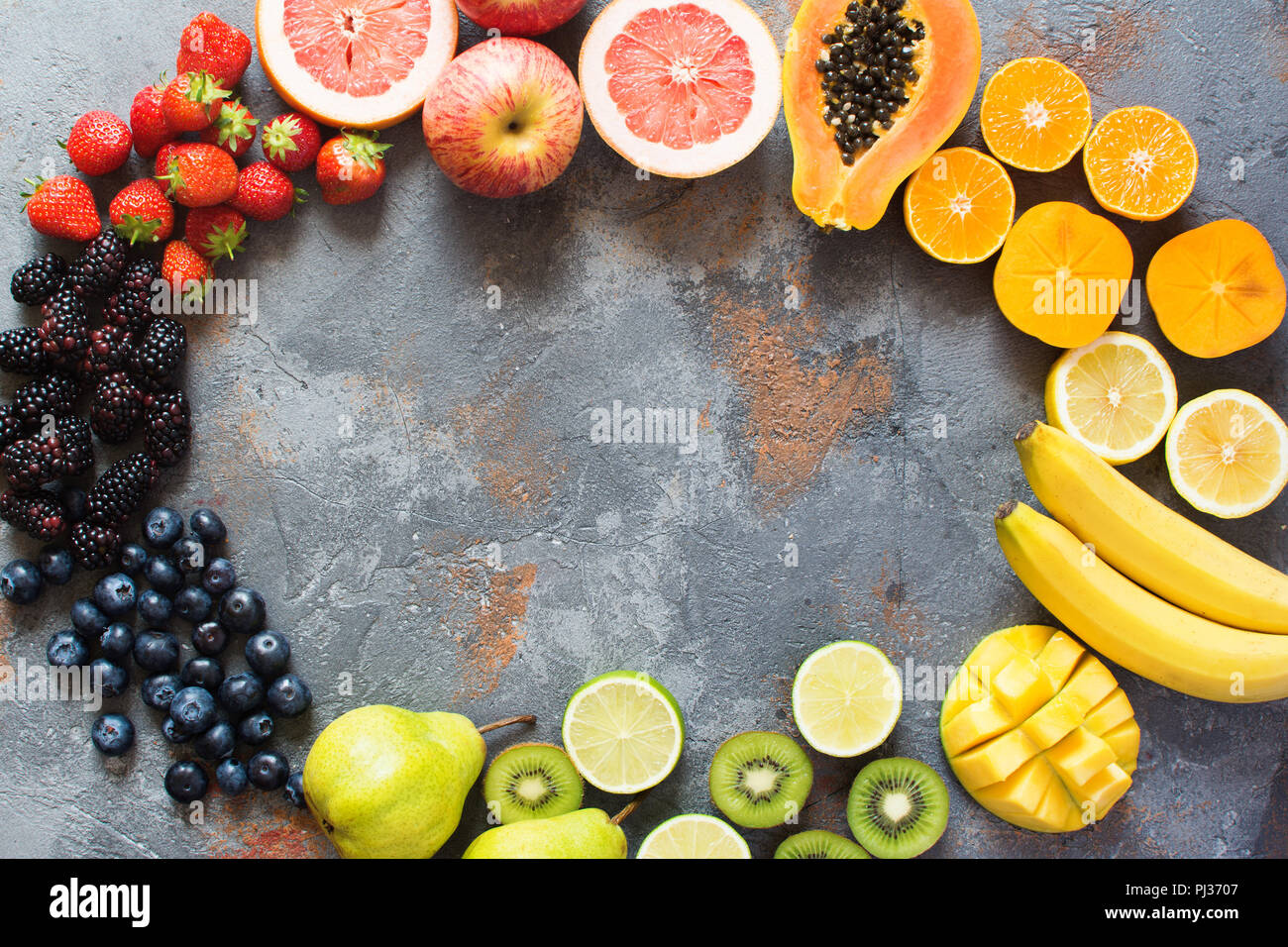 Rainbow colored fruits and berries arranged in a circle, on the grey stone background, copy space for text, selective focus Stock Photo