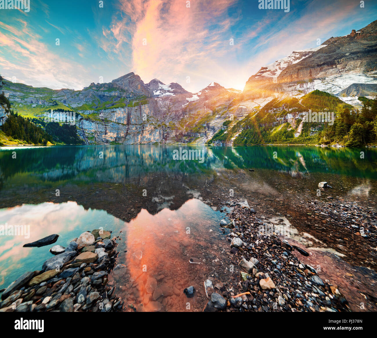 Colorful summer morning on unique lake - Oeschinen (Oeschinensee), UNESCO World Heritage Site. Switzerland, Europe. - Stock Image