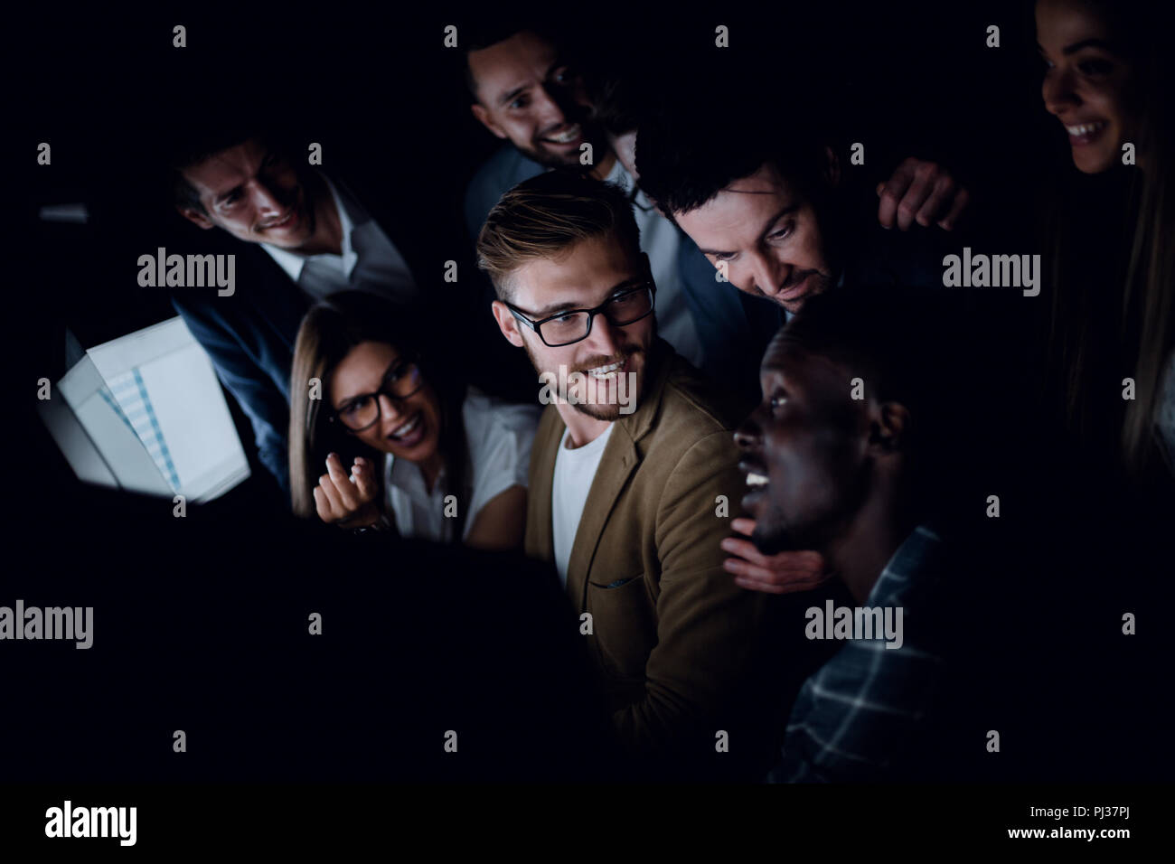 close up.successful business team sitting near the desktop in the evening - Stock Image
